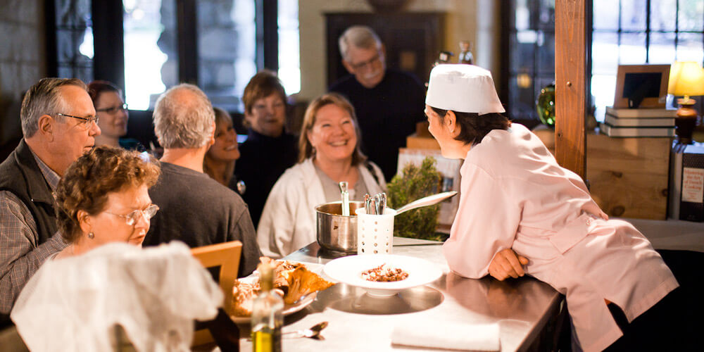 Chef talks with guests after a cooking demonstration