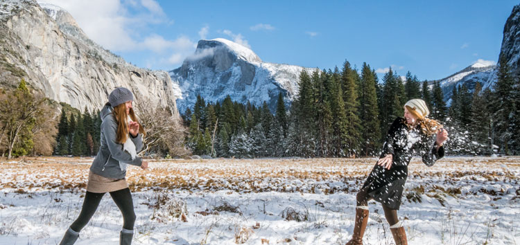Women having a snowball fight in Ahwahnee Meadow with Half Dome behind.