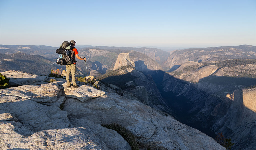 Hiker standing on Cloud's Rest looking at Half Dome