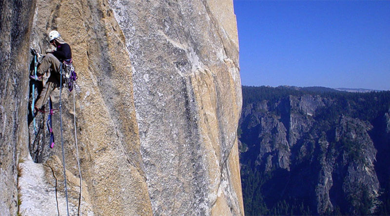 Aid Climbing on The Salathe Wall on El Capitan. You can see the webbing ladders called aiders or etriers used to make upward progress.