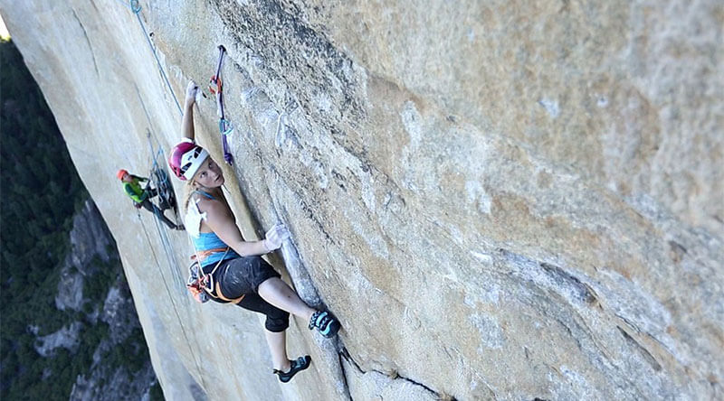 Emily Harrington free climbing Golden Gate (5.13 VI, 41 pitches) on El Capitan. Notice the belayer behind her managing the ropes she uses for protection and the gear near her left hand.