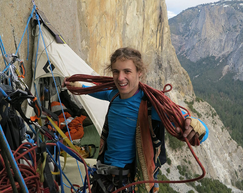 Climber Ryan Sheridan coils a rope high on El Capitan. Behind him you can see a portaledge where climbers spend the night.