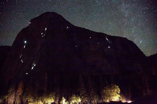 Climbers' headlamps high on El Capitan during the fall rock climbing season.