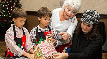 A family building a gingerbread house together