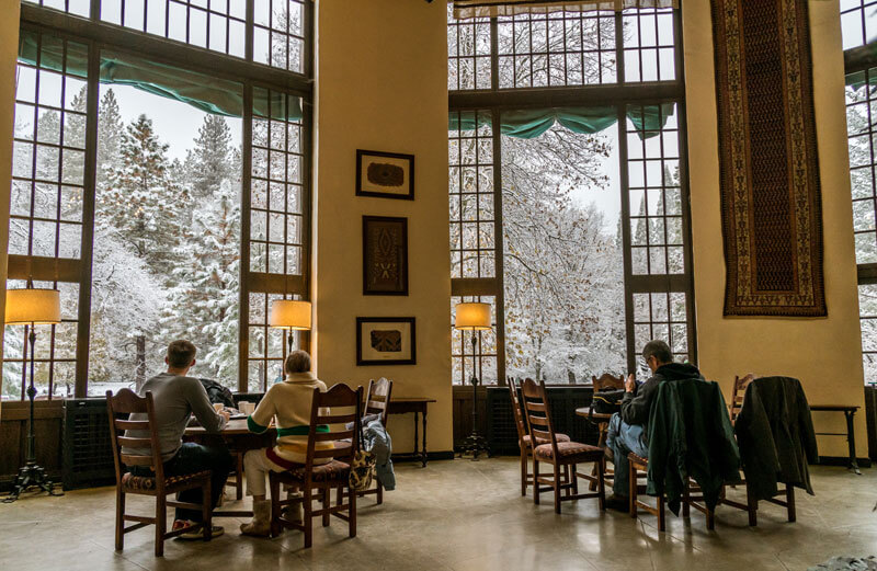 Enjoying snowy views from warm tables in The Ahwahnee