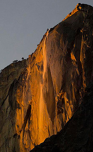 Horsetail fall and the wall behind glowing orange in the sunlight