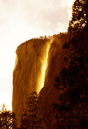 Horsetail fall flows bright against the dark cliffs behind