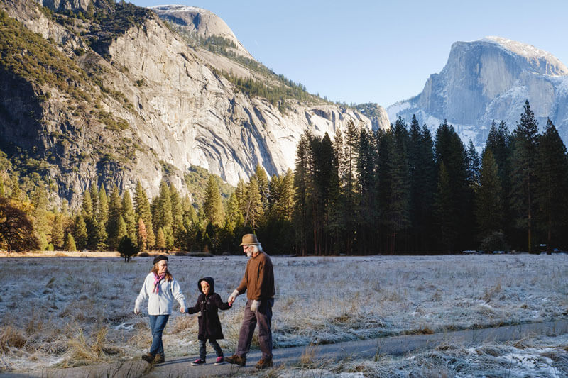 Grandparents walking with their grandchild with Half Dome in the background.