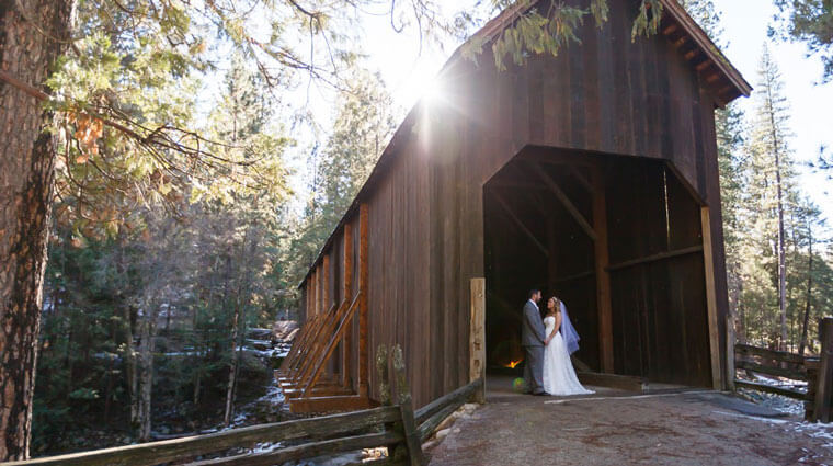 Wedding couple in Wawona's covered bridge