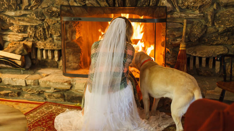 Bride and her dog in front of a fire