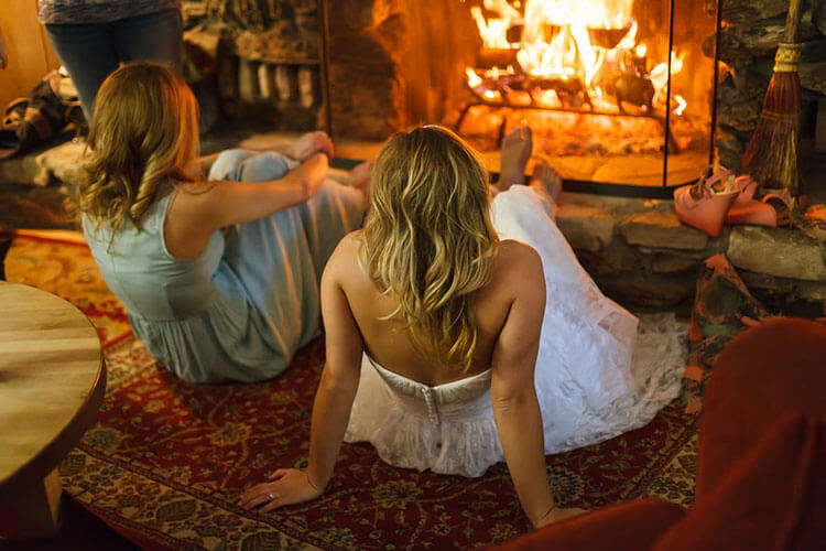 Bride & bridesmaid relaxing in front of a fire