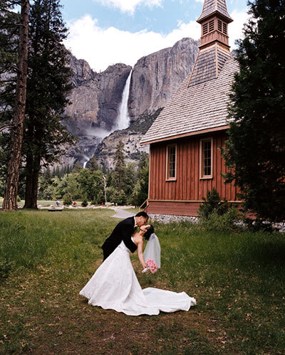 Wedding kiss by the Yosemite Valley Chapel with Yosemite Falls in the background.