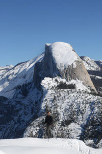 Skier at Washburn Point with Half Dome behind.