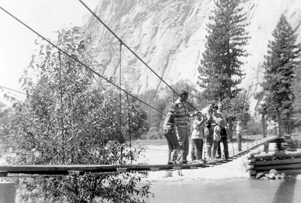 Historic image of a family lined up on the narrow swinging bridge in Yosemite Valley