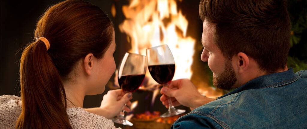 Couple toasting in front of a fireplace
