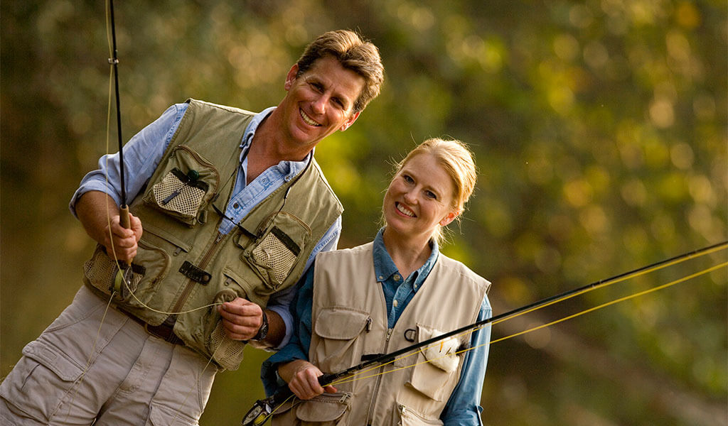 couple with fishing vests and fishing rod