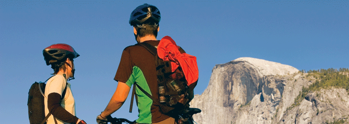 Two cyclists looking up at Half Dome
