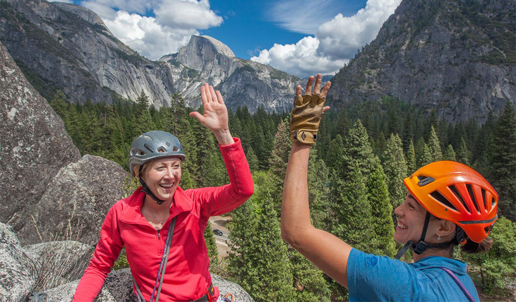 Two women rock climbers giving each other a high-five.